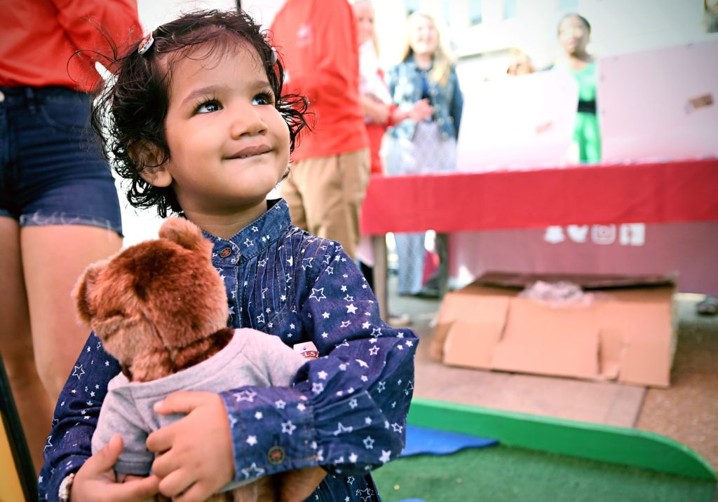 little girl clutching debate teddy bear